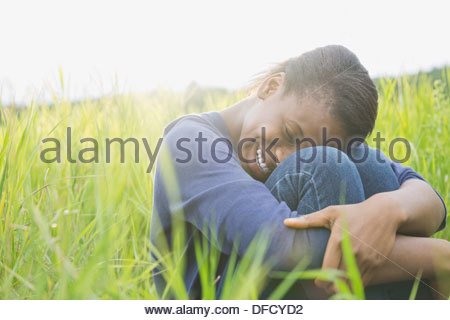 Happy teenage girl sitting outdoors in field - Stock Photo