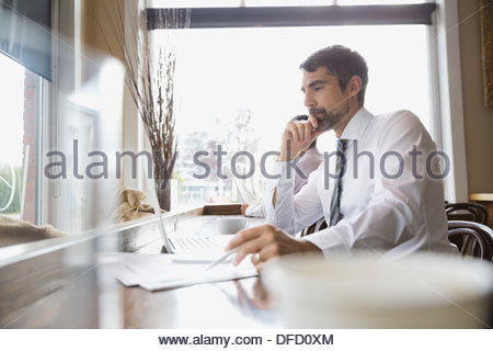 Businessman looking at laptop in cafe - Stock Photo