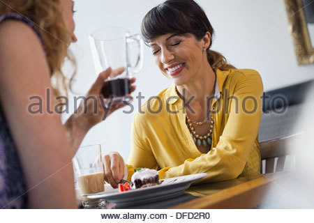 Female friends laughing while dining out - Stock Photo