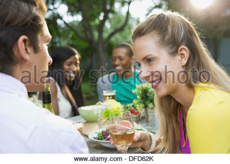 Happy couple having meal with friends in backyard - Stock Photo