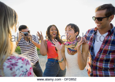 Friends looking at woman blowing bubble gum - Stock Photo