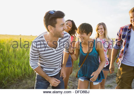 Group of friends laughing outdoors - Stock Photo