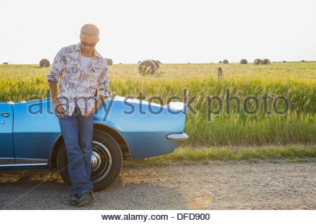 Man leaning against blue convertible - Stock Photo