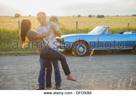 Romantic couple dancing on country road - Stock Photo