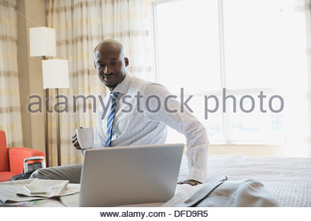 Businessman looking at laptop in hotel room - Stock Photo