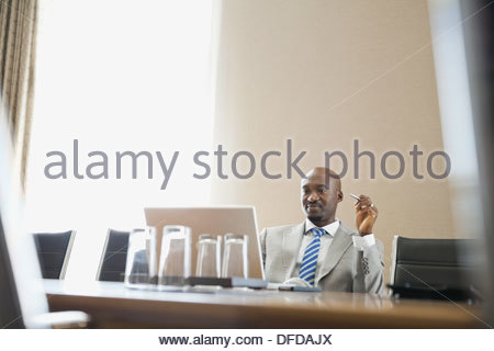 Businessman looking at laptop in hotel conference room - Stock Photo