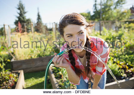 Woman drinking water from garden hose - Stock Photo