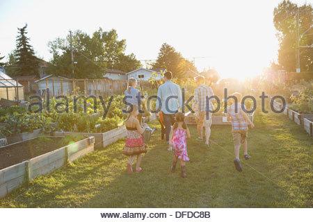 Rear view of group walking through community garden - Stock Photo