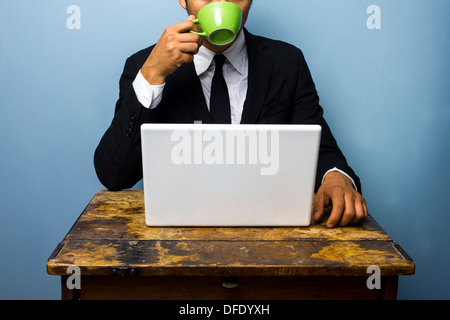Young businessman is drinking coffee and working on his laptop at an old desk - Stock Photo
