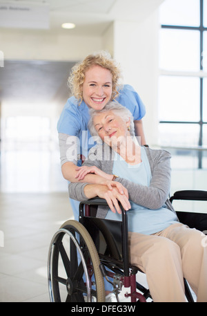 Portrait of smiling nurse and elderly patient in wheelchair - Stock Photo