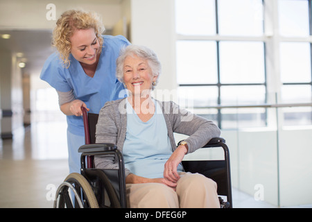 Nurse and aging patient smiling in hospital corridor - Stock Photo