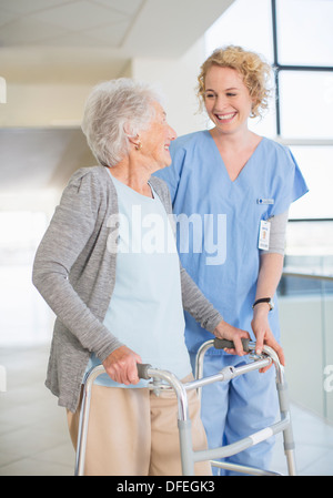 Senior patient with walker smiling at nurse in hospital corridor - Stock Photo