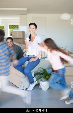 Parents watching children run around living room in new house - Stock Photo