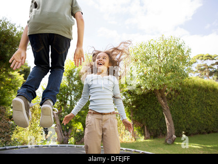 Children jumping on trampoline in backyard - Stock Photo