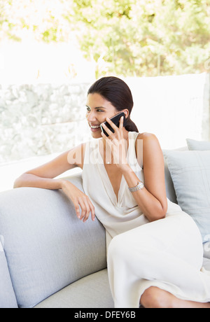 Woman talking on cell phone in livingroom - Stock Photo