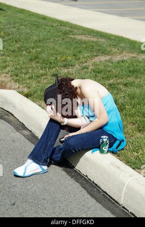 Drunken teen female sits on the edge of a street curb after drinking too much alcohol - Stock Photo