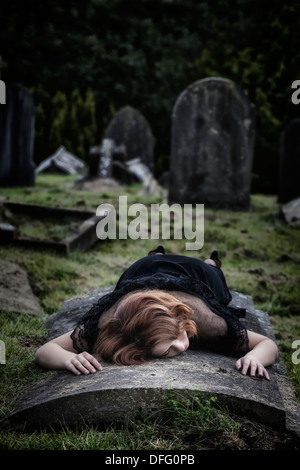 a woman is lying on a tomb - Stock Photo