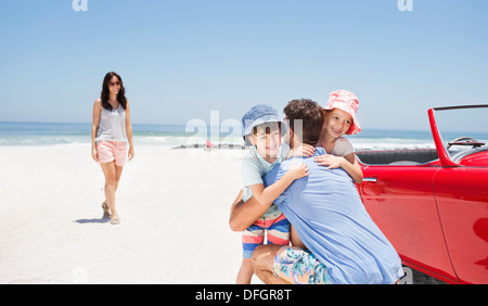 Father hugging daughter and son near convertible at beach - Stockfoto