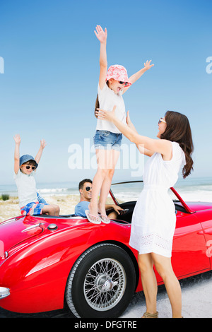 Girl jumping into mother's arms from convertible at beach - Stock Photo
