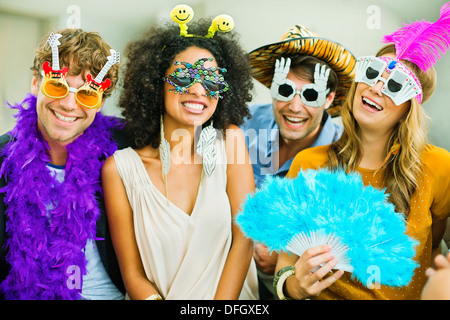 Smiling friends wearing silly glasses - Stock Photo