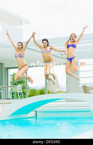 Women jumping into swimming pool - Stock Photo