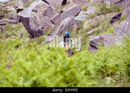 Mountain biker on Stanage Edge in Derbyshire Peak District  National Park. England UK - Stock Photo