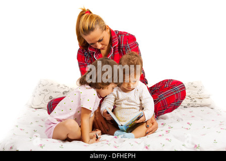 Mother reading a bedtime story to her kids in bed - Stock Photo