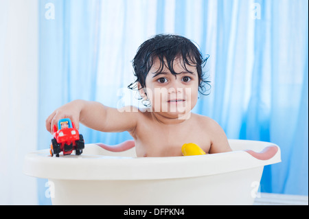 Baby boy playing with toys in a bathtub - Stock Photo