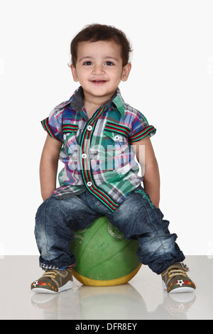 Portrait of a 5 year old indian boy seating on ball - Stock Photo