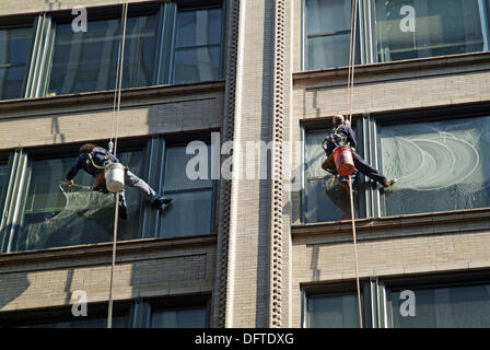Window washers work at extreme heights to clean windows on tall buidings and skyscrapers in Chicago, Illinois. USA. - Stock Photo