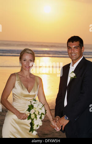 wedding couple on the beach with sunset view in the background - Stockfoto
