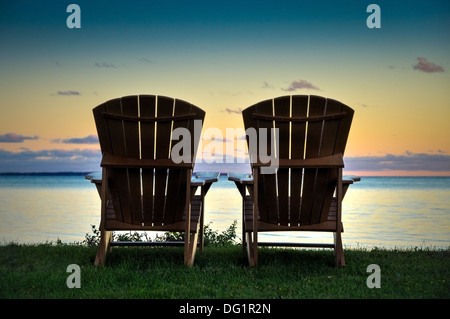 two Adirondack chairs on the shore of Lake Ontario New York usa - Stock Photo