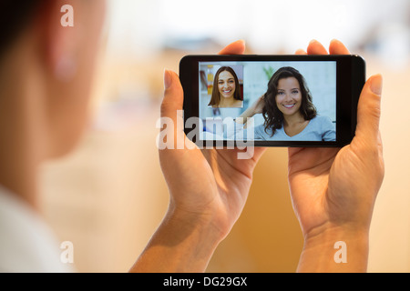 Woman chatting with her friend on smartphone - Stock Photo