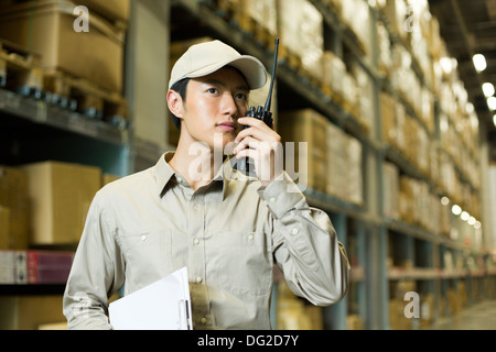 Young logistics staff using walkie-talkie in warehouse - Stock Photo