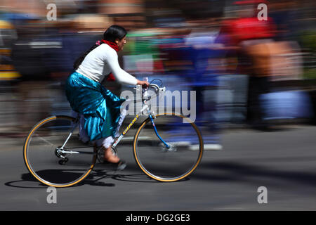 El Alto, Bolivia. 12th Oct, 2013.  A competitor rides past spectators as she takes part in a Cholitas Bicycle Race - Stock Photo