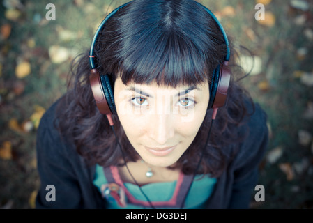 young beautiful woman listening to music at the park in autumn - Stock Photo