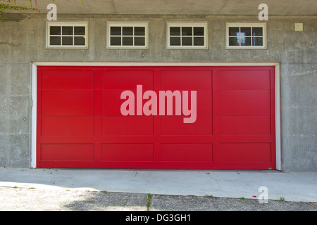 Large red garage door and four windows. - Stock Photo