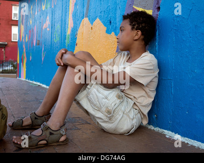 Young boy leaning,sitting against a cheerily painted wall - Stockfoto