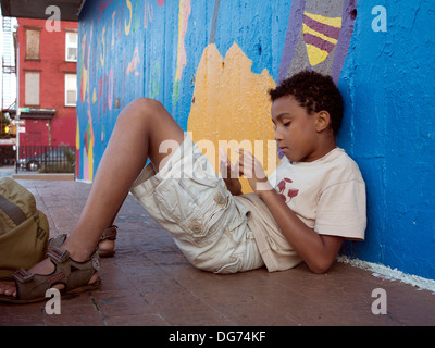 Young boy half laying half sitting on the floor against a cheerily painted wall. - Stock Photo