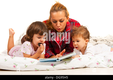 Mother reading bedtime story to her children in bed - Stock Photo