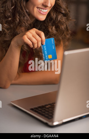 Closeup on credit card in hand of woman usign laptop - Stock Photo