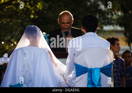 Young couple sitting in chairs in wedding clothes being married in the central plaza of Granada  in Nicaragua on - Stockfoto