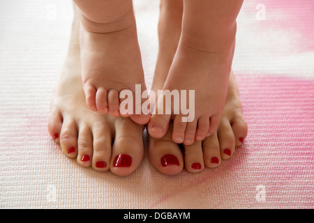 Baby toes on her mother's feet - Stock Photo