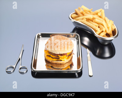 Burger and fries sitting in surgical trays illustrating unhealthy diet - Stock Photo