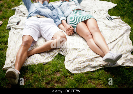 Young couple lying in park and holding hands - Stock Photo