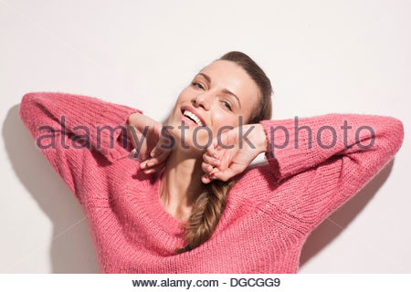 Young woman wearing pink sweater and stretching - Stock Photo