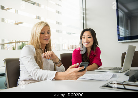 Young businesswomen looking at smartphone in conference room - Stock Photo