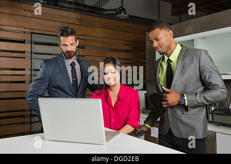 Young business colleagues looking at laptop in meeting - Stock Photo