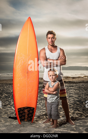 Young man and son standing with surfboard on beach, portrait - Stock Photo