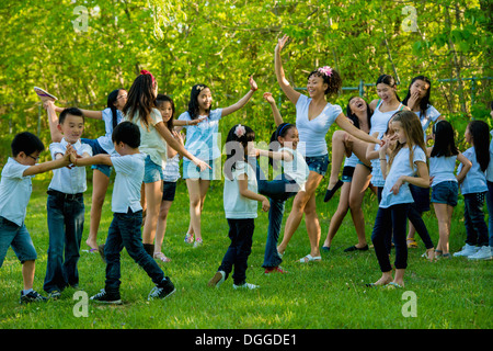 Large group of children dancing in park - Stock Photo